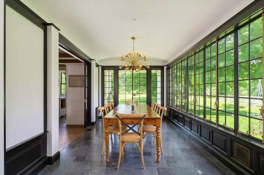 """A whole wall of vintage Hopes steel-framed casement windows give the dining room a conservatory feel. Its Belgium bluestone flooring features radiant heat. Both men would stand on this private lane in disbelief and wonder at the sight of this modern day masterpiece that also honors the past. The house has undergone several major renovations, including one in 1916 by famed local architect Cameron Clark, and another early in the new millennium that earned its then-homeowners a Distinguished Achievement Award from the Southport Conservancy in 2003 for the """"careful and sympathetic preservation of the original architectural features of this important Southport landmark."""" With that in mind, what recognition might the current owners get for their recent expansion and overhaul, which preserved the home's historic integrity and period details while imbuing it with luxurious modern features?  Photo: Kyle P Norton / KYLE P NORTON"""