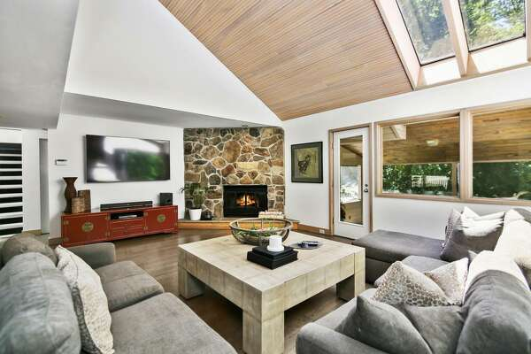 The sizable two-story living room features a wall of stone housing a fireplace, skylights, a wood accented vaulted ceiling, interior balcony, and a door to a large sunroom.