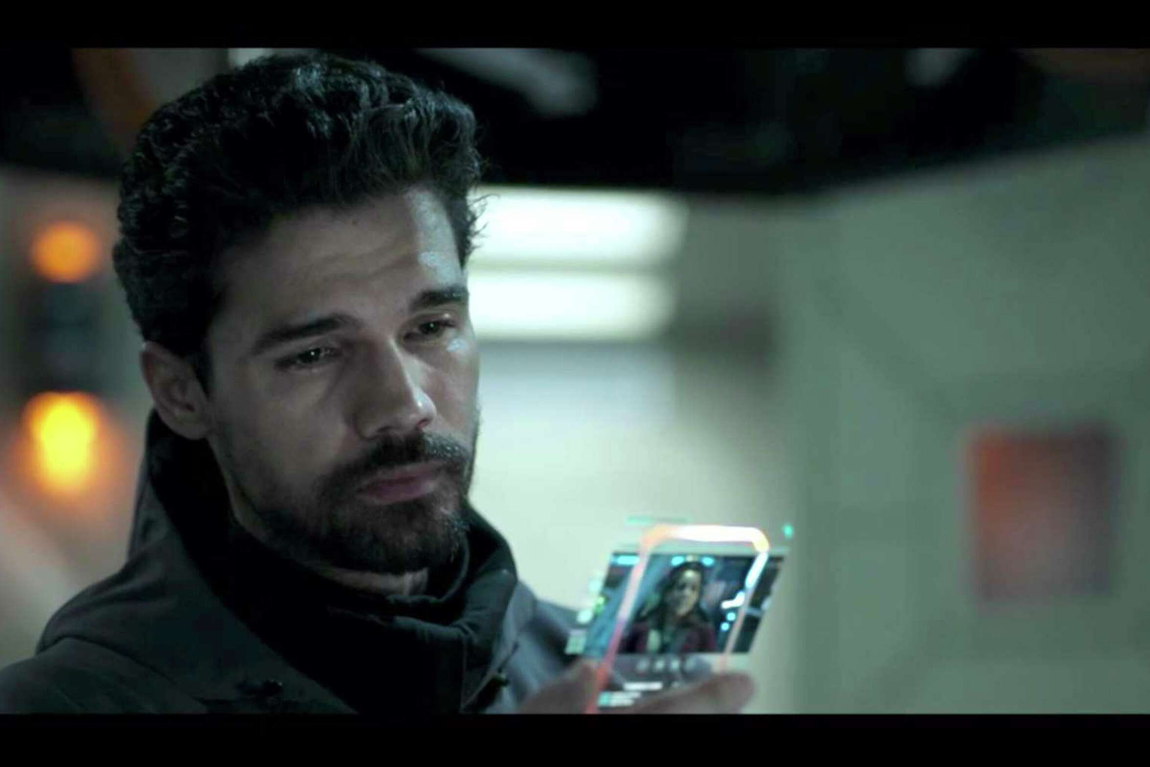 """Actor Steven Strait, as James Holden, studies a hand terminal, the futuristic communications devices seen in the Amazon Prime Video sci-fi series """"The Expanse."""""""