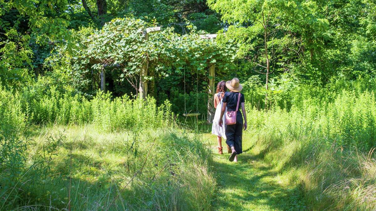 Visitors head down a trail at I-Park in East Haddam. I-Park's art residents over the years have created ephemeral works that respond to (and reflect) the property's natural and built environments.