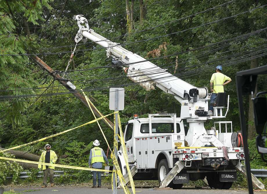 A utility crew works to erect a downed pole on Taylor Street on August 7, 2020 in Stamford, Connecticut. Many out of state crews have been brought in to assist Eversource in restoring power to the region and help with clean up of storm debris left in the wake of Tropical Storm Isaias Photo: Matthew Brown, Hearst Connecticut Media