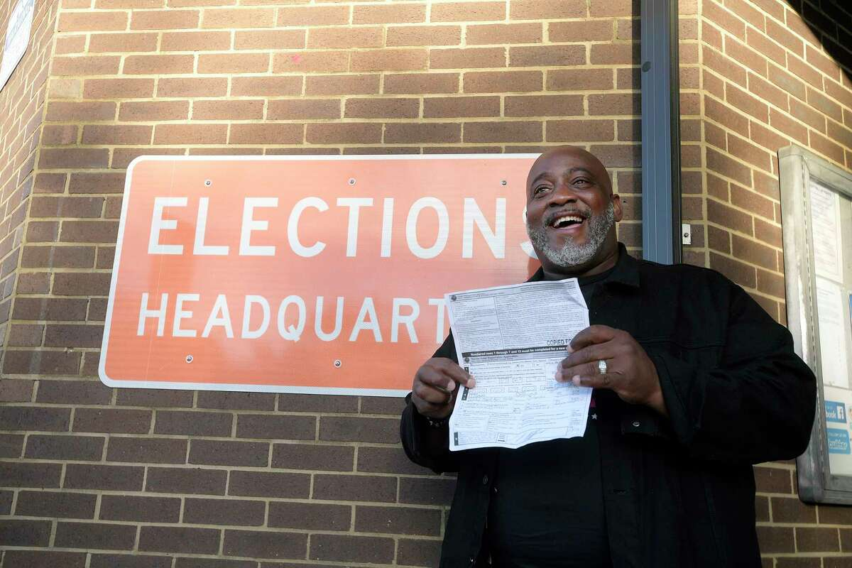Desmond Meade displays a copy of his voter registration form outside the Orange County Supervisor of Elections office in Orlando on Jan. 8, 2019, after registering to vote.