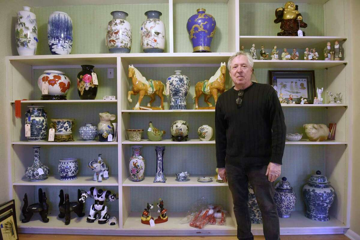 Andy Geller, owner of New Scotland Antiques, stands in front of shelves of collectibles in a home where he is running an estate sale on Friday, March 13, 2020 in Menands, N.Y. (Lori Van Buren/Times Union)
