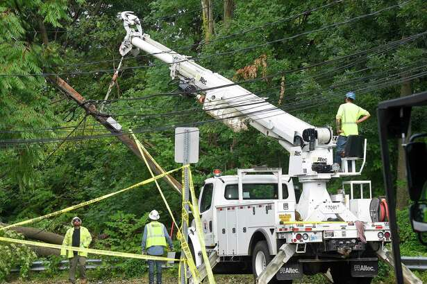 A utility crew works on a downed pole on Aug. 7, 2020, in Stamford, Conn. Broadband companies are absorbing complaints from customers, despite not being able to work on restoring lines before getting the OK from electric utilities.