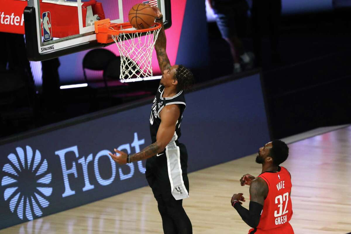 LAKE BUENA VISTA, FLORIDA - AUGUST 11: DeMar DeRozan #10 of the San Antonio Spurs dunks the ball in front of Jeff Green #32 of the Houston Rockets during the first half of a NBA basketball game at The Field House at ESPN Wide World Of Sports Complex on August 11, 2020 in Lake Buena Vista, Florida. NOTE TO USER: User expressly acknowledges and agrees that, by downloading and or using this photograph, User is consenting to the terms and conditions of the Getty Images License Agreement. (Photo by Kim Klement-Pool/Getty Images)