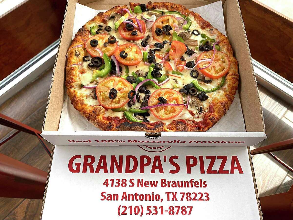 A specialty pizza called Grandpa's Pizza incorporates tomatoes, mushrooms, green bell peppers, onions, black olives and basil at Grandpa's Pizza.