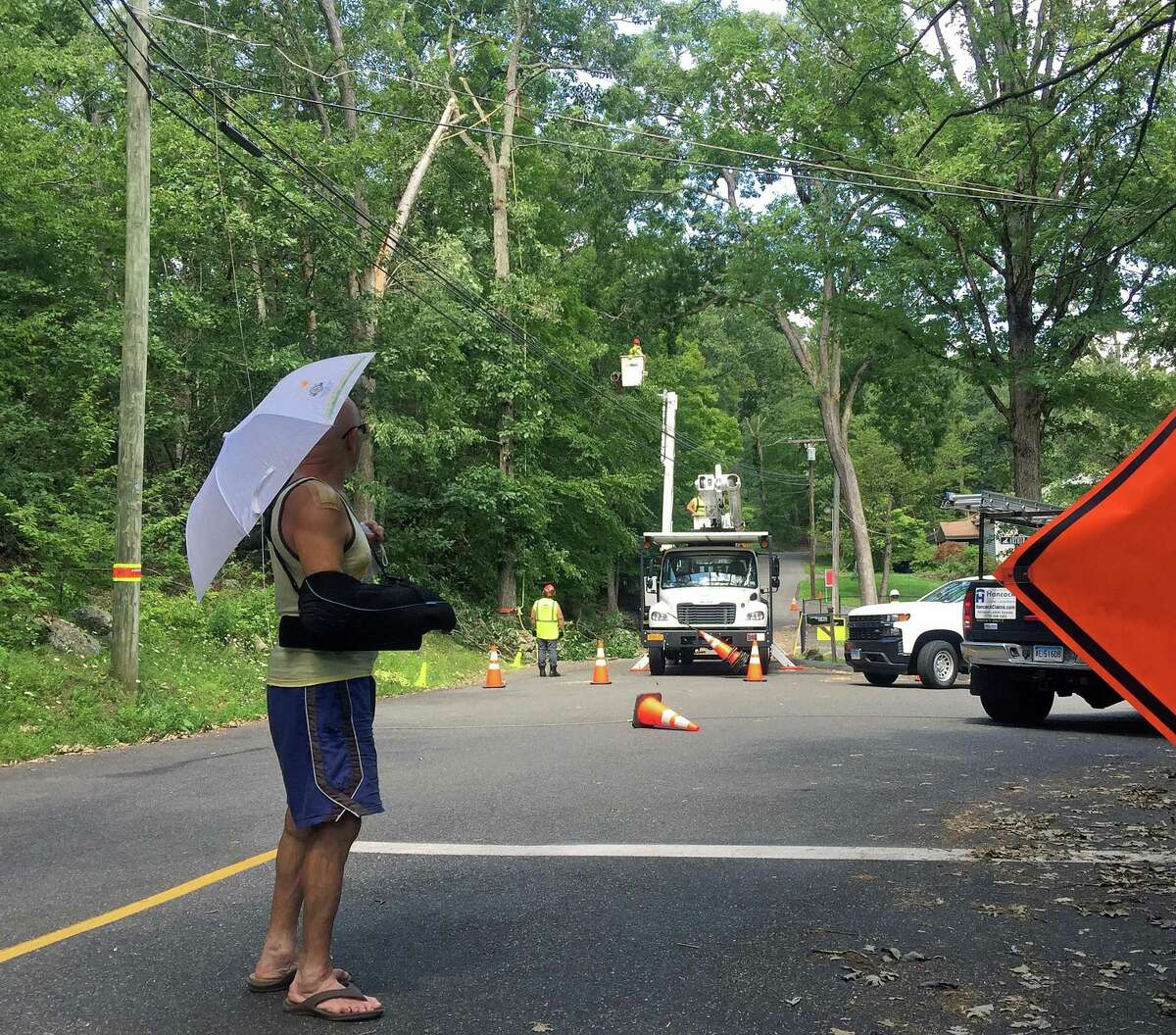 Bo Detch, a resident of Danbury's Lake Waubeeka community who was without power for eight days, watches line workers restoring power on Wednesday Aug. 12, 2020.