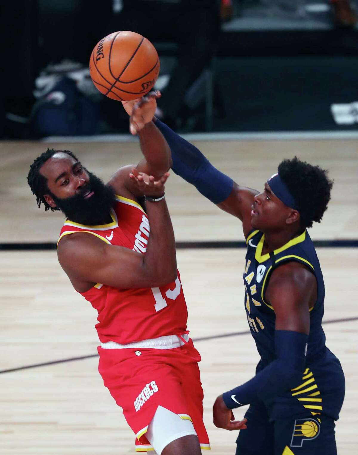 Houston Rockets guard James Harden (13) passes the ball away from Indiana Pacers guard Victor Oladipo (4) in the first half of an NBA basketball game Wednesday, Aug. 12, 2020, in Lake Buena Vista, Fla. (Kim Klement/Pool Photo via AP)