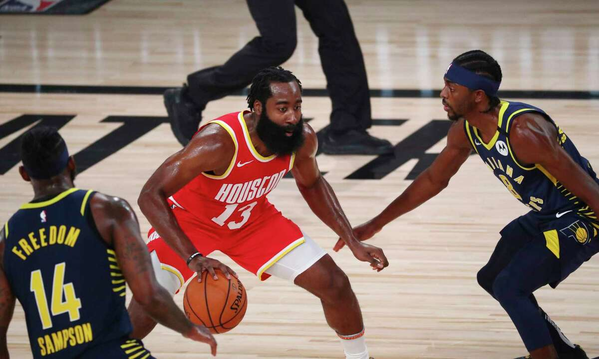 Houston Rockets guard James Harden (13) dribbles the ball between Indiana Pacers forward JaKarr Sampson (14) and forward Justin Holiday (8) in the first quarter of an NBA basketball game Wednesday, Aug. 12, 2020, in Lake Buena Vista, Fla. (Kim Klement/Pool Photo via AP)