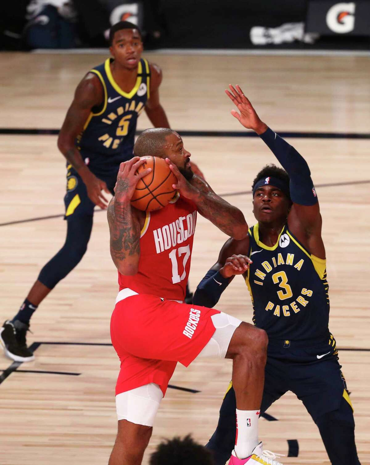 Houston Rockets forward P.J. Tucker (17) drives to the basket against Indiana Pacers guard Aaron Holiday (3) in the first half of an NBA basketball game Wednesday, Aug. 12, 2020, in Lake Buena Vista, Fla. (Kim Klement/Pool Photo via AP)
