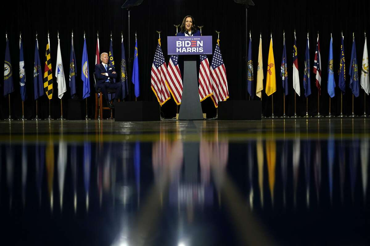 Democratic presidential candidate former Vice President Joe Biden listens as his running mate Sen. Kamala Harris, D-Calif., speaks during a campaign event at Alexis Dupont High School in Wilmington, Del., Wednesday, Aug. 12, 2020. (AP Photo/Carolyn Kaster)