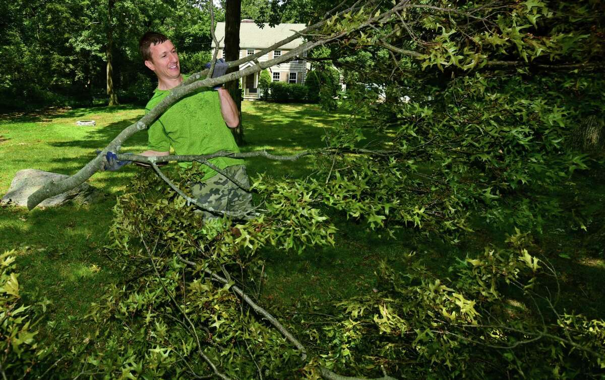 David Bencivenga clears his lawn of downed branches at his home on Wood Acre Rd. Wednesday, August 12, 2020, in Norwalk, Conn. A week after tropical storm Isias some residents are still without power.