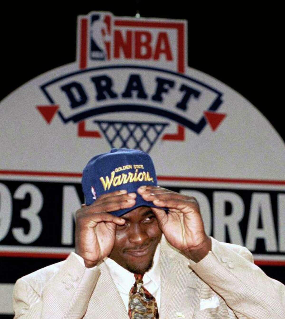 Michigans Chris Webber puts on a Golden State Warriors hat after Webber was traded to Golden State during the NBA draft at the Palace, Wednesday, June 30, 1993, Auburn Hills, Mich. Webber was the first selection in the draft by the Orlando Magic, then he was traded to Golden State when the Warriors selected, Anfernee Hardaway as the third pick. (AP Photo/Lennox Mclendon)