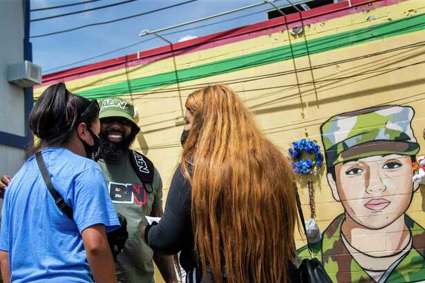 Lupe Guillén and her sister Mayra Guillén meet up with rapper Trae tha Truth, center, at a mural and makeshift memorial in honor of Vanessa Guillén to receive a gift from him on Wednesday, Aug. 12, 2020, in Houston.