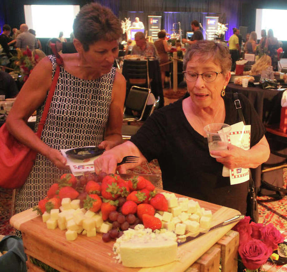In this August 2019 file photo, Ilene Butts, left, of Edwardsville, and Pat Davis of Troy look over cheese and fruit while in a serving line at Farm-to-Table, a fundraiser for the Metro East Chapter of the American Cancer Society held last year at Gateway Center in Collinsville. The event featured entertainment, food by local restaurants and a number of other activities. The goal was $70,000 to be used for research and providing services for local cancer patients.