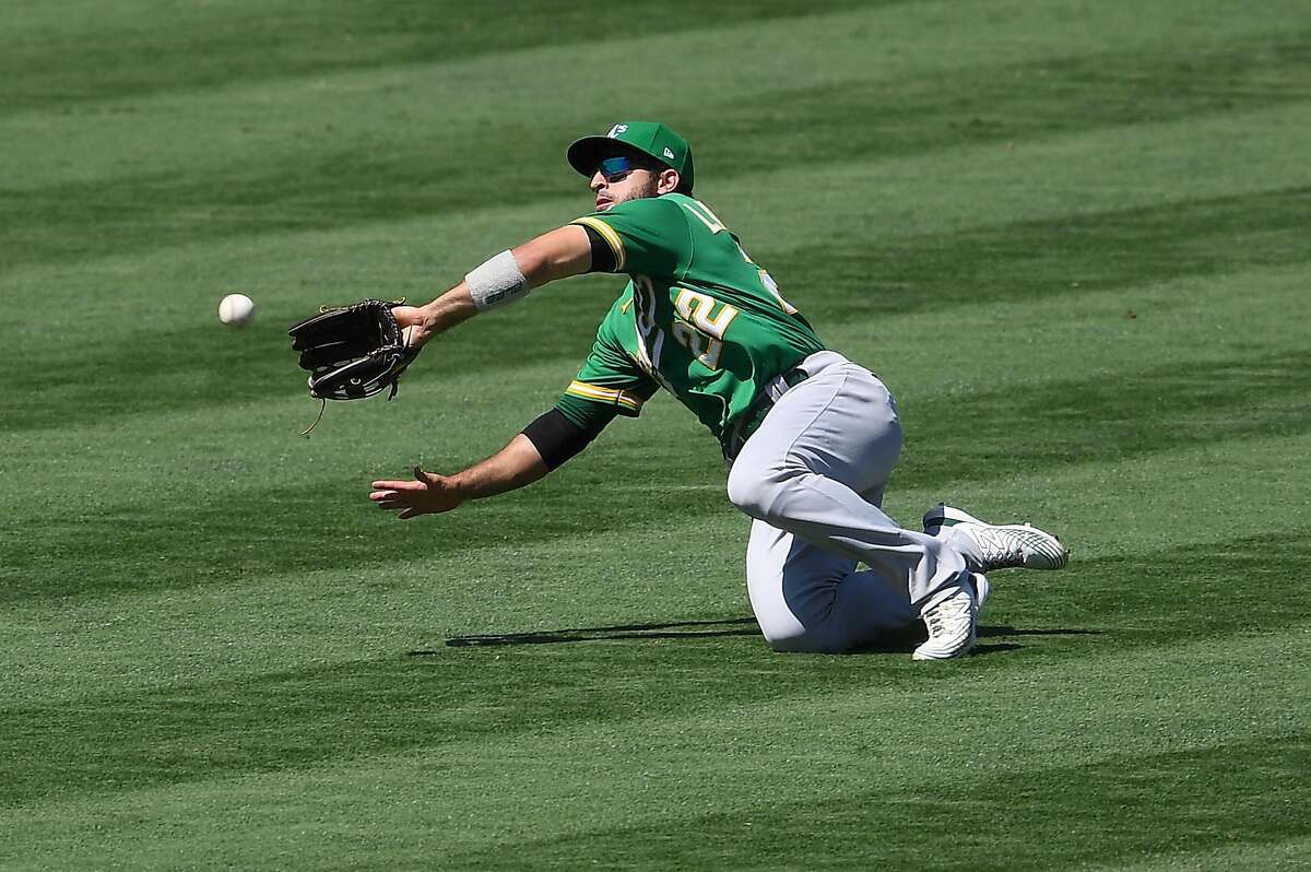 ANAHEIM, CA - AUGUST 12: Ramon Laureano #22 of the Oakland Athletics makes a diving catch off a ball hit by Jo Adell #59 of the Los Angeles Angels in the fifth inning of the game at Angel Stadium of Anaheim on August 12, 2020 in Anaheim, California. (Photo by Jayne Kamin-Oncea/Getty Images)