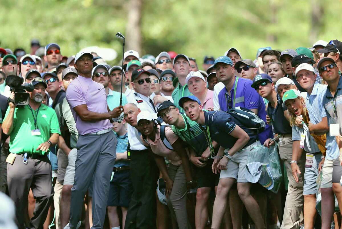 FILE - In this April 13, 2019, file photo, Tiger Woods hits from the gallery along the 11th fairway during the third round of the Masters golf tournament at Augusta National in Augusta, Ga. The Masters, the major known as much for the roars of the crowd as the raw beauty of Augusta National, will be on mute this year. The club decided Wednesday, Aug. 12, 2020, there will be no spectators. (Curtis Compton/Atlanta Journal-Constitution via AP, File)