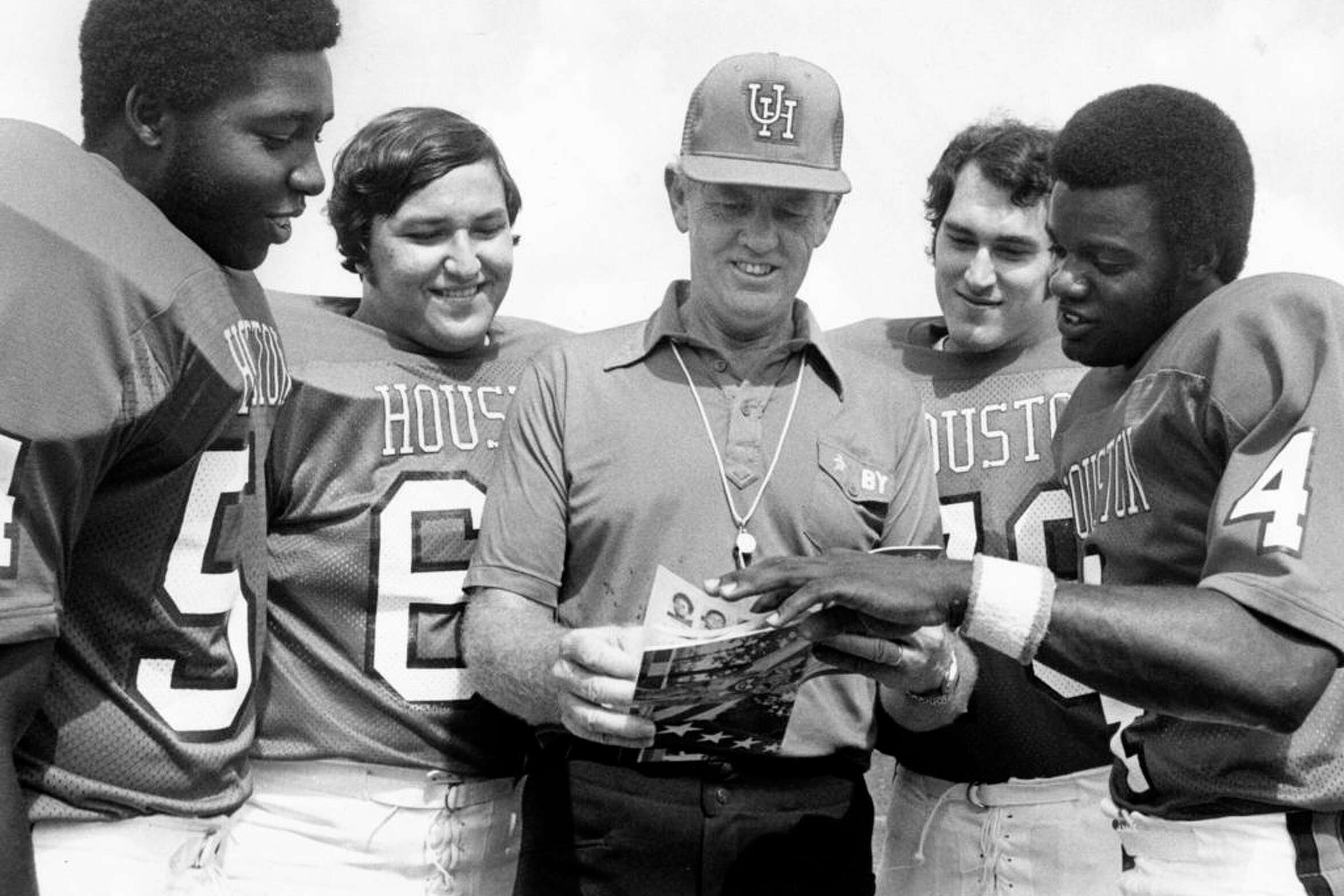 In 1977, Bill Yeoman browses through the University of Houston press guide as Cougar co-captains look on. From left, they are Vincent Greenwood, Ramon Rosales, Kevin Rollwage and Danny Davis.