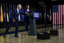 Presumptive Democratic presidential nominee Joe Biden grabs his mask from the podium after introducing his running mate, Sen. Kamala Harris, D-Calif., at Alexis I. DuPont High School in Wilmington, Del., on Wednesday, Aug. 12, 2020.