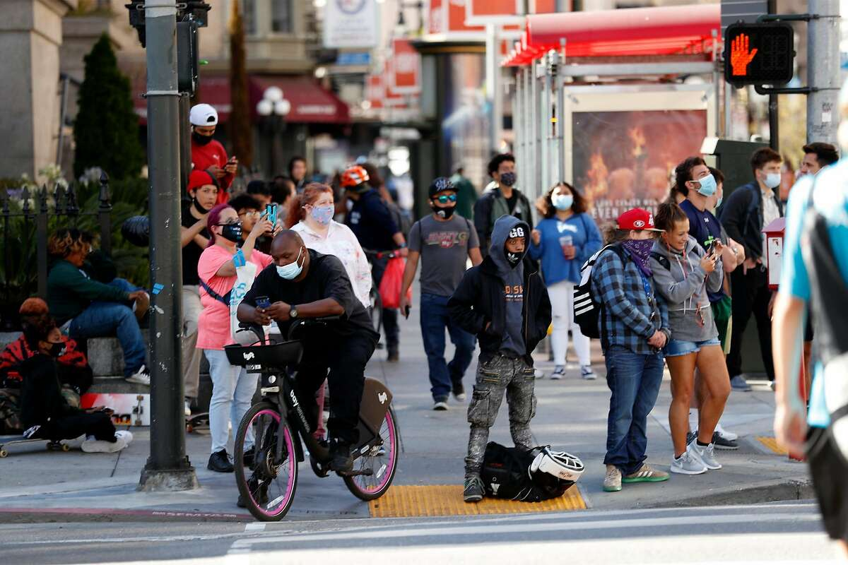 Onlookers stand at 5th and Mission as San Francisco Police search for shooting suspect in parking garage across the street in San Francisco, Calif., on Wednesday, August 12, 2020.