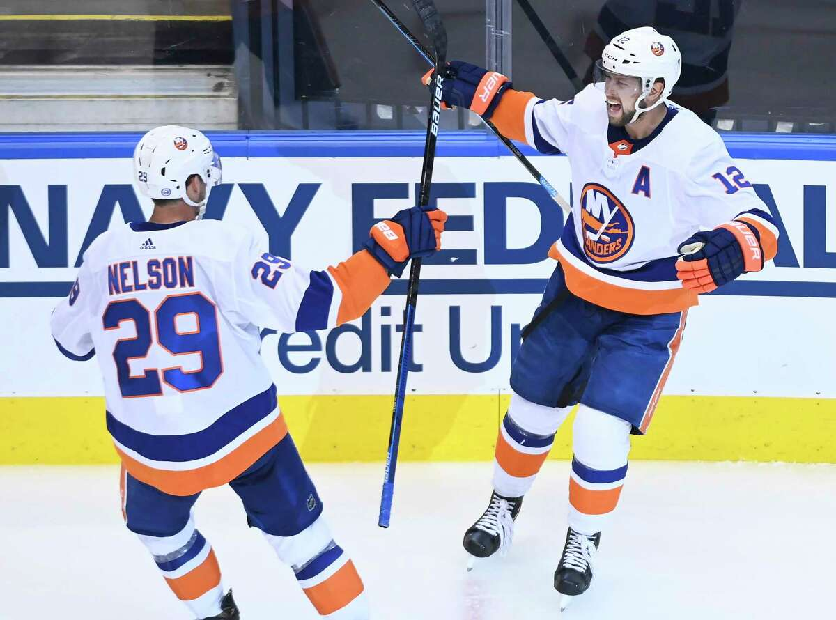 New York Islanders right wing Josh Bailey (12) celebrates his goal with teammate Brock Nelson (29) after scoring against the Washington Capitals during the third period of an NHL Eastern Conference Stanley Cup playoff hockey game in Toronto, Ontario, on Wednesday, Aug. 12, 2020. (Nathan Denette/The Canadian Press via AP)