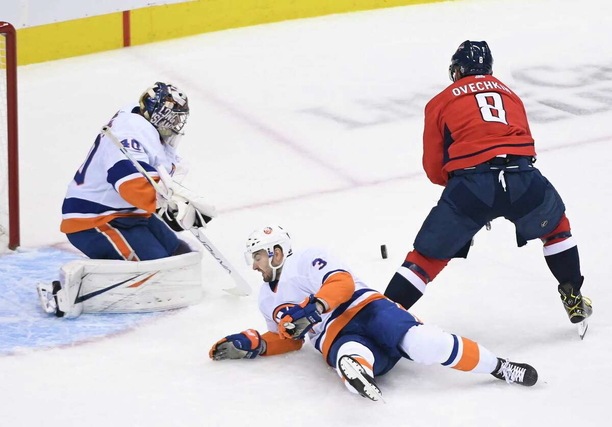 New York Islanders goaltender Semyon Varlamov (40) stops Washington Capitals left wing Alex Ovechkin (8) as Capitals defenseman Nick Jensen (3) falls to the ice during the first period of an NHL Eastern Conference Stanley Cup hockey playoff game in Toronto, Wednesday, Aug. 12, 2020. (Nathan Denette/The Canadian Press via AP)