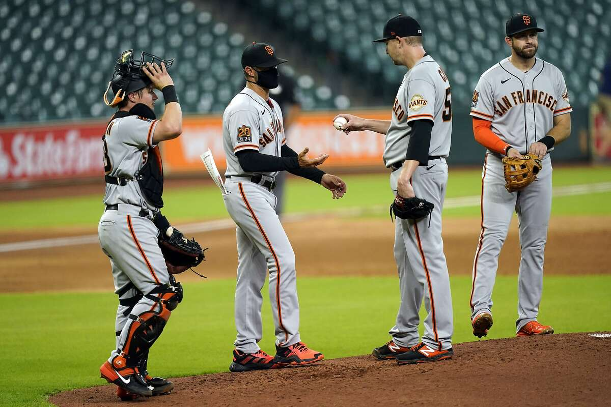 San Francisco Giants manager Gabe Kapler, second from left, takes the ball from starting pitcher Trevor Cahill, second from right, as he pulls him during the second inning of a baseball game against the Houston Astros Wednesday, Aug. 12, 2020, in Houston. Catcher Tyler Heineman is left and third baseman Evan Longoria is right. (AP Photo/David J. Phillip)