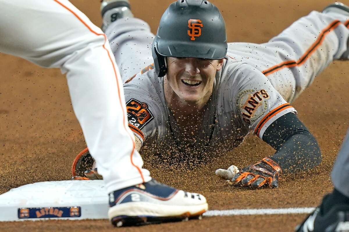 San Francisco Giants' Mike Yastrzemski dives toward third base after hitting a triple against the Houston Astros during the first inning of a baseball game Wednesday, Aug. 12, 2020, in Houston. (AP Photo/David J. Phillip)