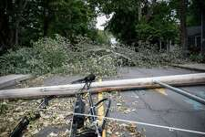 Power lines and poles lie in a roadway beside a fallen tree brought down by Tropical Storm Isaias, Friday, Aug. 7, 2020, in Westport, Conn.