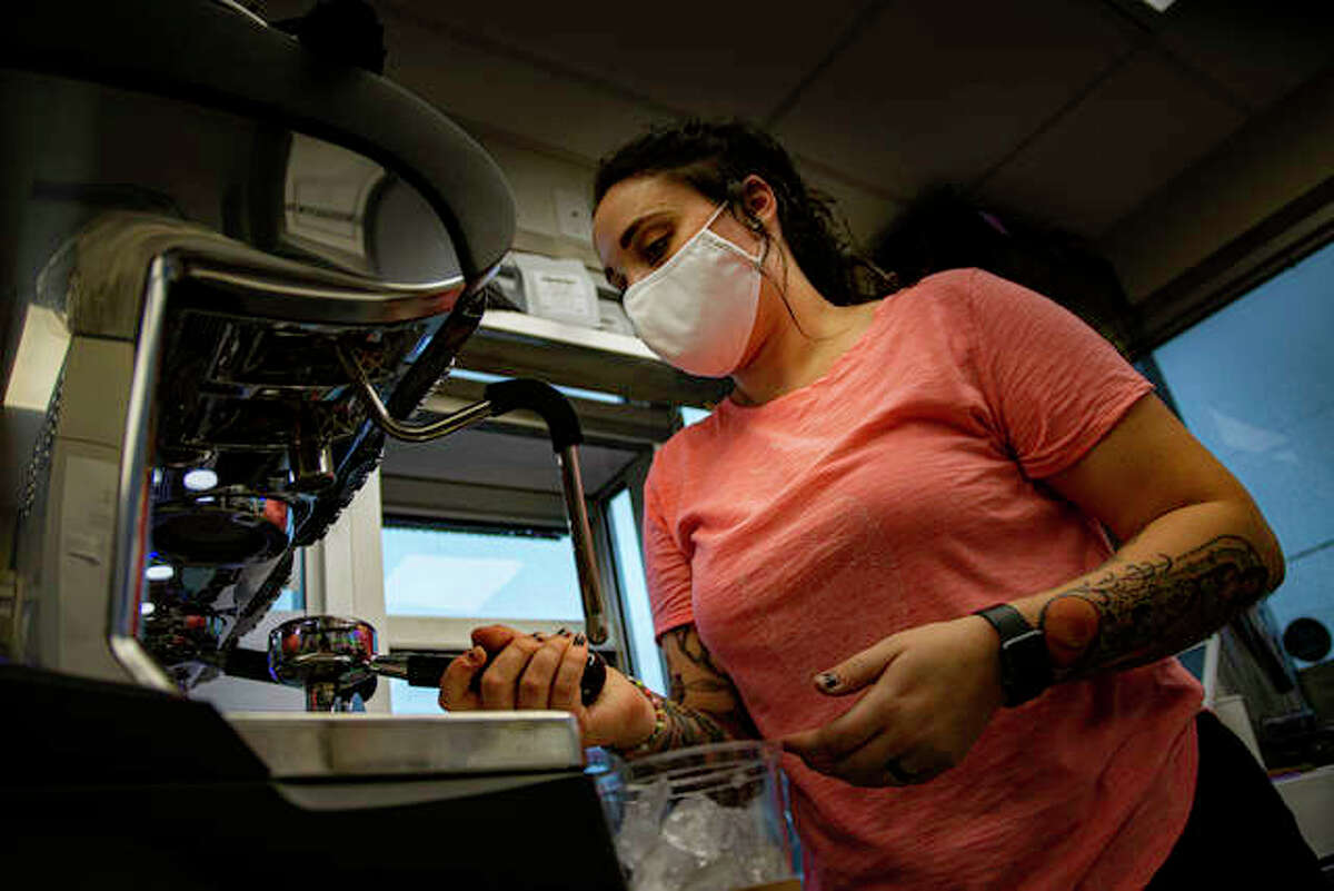 A Coffee Box barista works on an order placed during the shop's soft opening Wednesday morning.