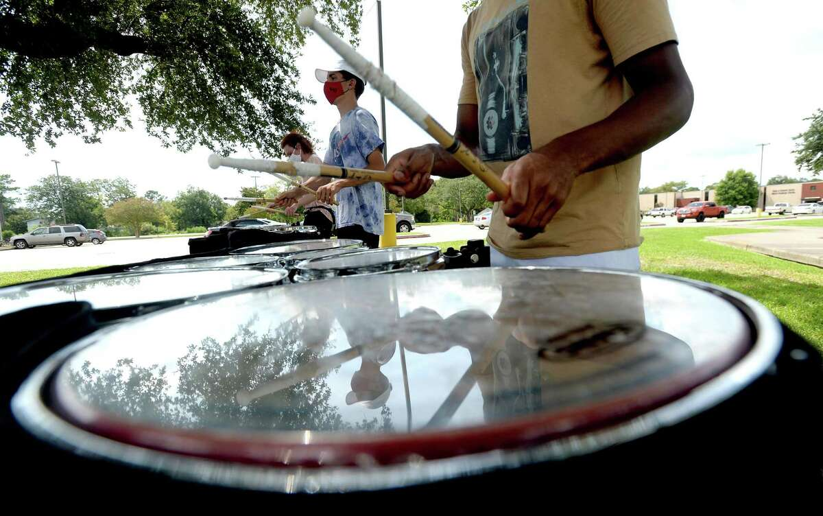Members of Lamar University's marching band drum line, including Lakota Jaton (center), rehearse beneath the shade of trees as they begin to prepare for the hopeful start of their performance season. Photo taken Wednesday, August 12, 2020 Kim Brent/The Enterprise