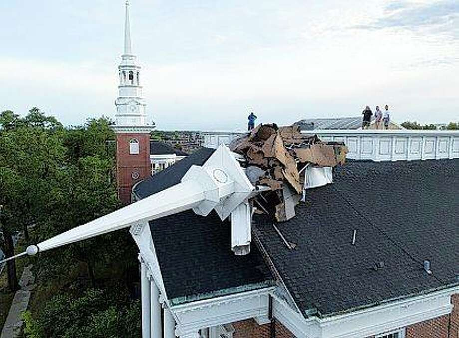 College Church officials check out the damage from the church's rooftop in Wheaton after the steeple was toppled Monday during a storm in Chicago's northwest suburbs. Monday's storms left a trail of damage across the Midwest. Photo: Mark Welsh | Daily Herald Via AP