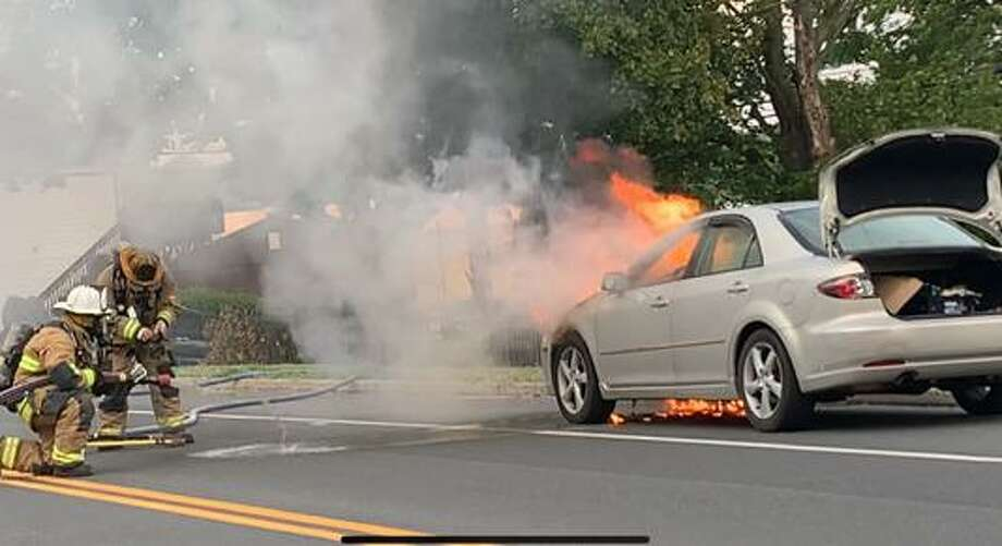 Shelton firefighters battle a car fire on River Road Wednesday, Aug. 12. Photo: Shelton Fire Department / Contributed Photo / Connecticut Post