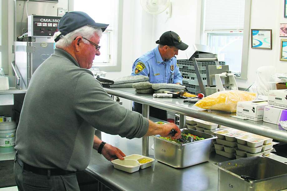 A Manistee County's Meals on Wheels volunteer prepares meals in 2018. The program serves nearly 250 seniors (mostly home-bound) Monday through Friday, via five delivery routes and four congregate meal sites and a team of dedicated volunteers. Photo: File Photo