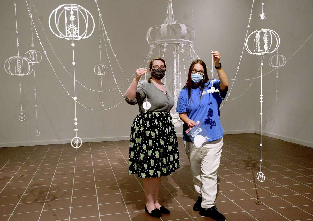 Art Museum of Southeast Texas staffers Kayleigh Thompson (left) and Christle Feagin show one of the craft projects, this one inspired by featured artist Kana Harada, they will hand out this Saturday during a