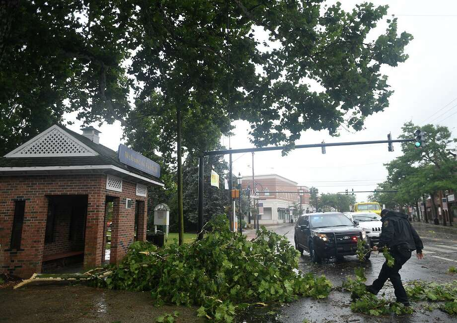 A Fairfield police officer uses his foot to clear fallen branches from the Post Road as Tropical Storm Isaias brings high winds to Fairfield, Conn. on Tuesday, August 4, 2020. Photo: Brian A. Pounds / Hearst Connecticut Media / Connecticut Post