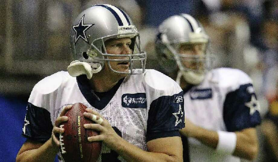 Backup quarterback Jon Kitna (front) warms up with starter Tony Romo during training camp at the Alamodome.