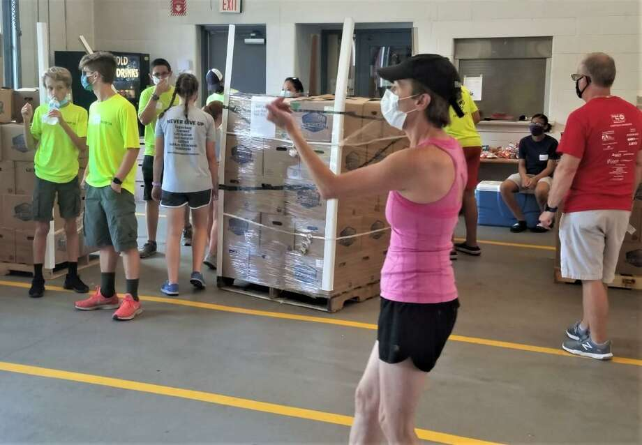 Volunteers from the Middlesex United Way and St. Vincent dePaul Middletown's Amazing Grace Food Pantry helped unload a truck containing 1,400 20-pound boxes of fresh vegetables and fruit in Cromwell recently. Photo: Contributed Photo / Middlesex United Way
