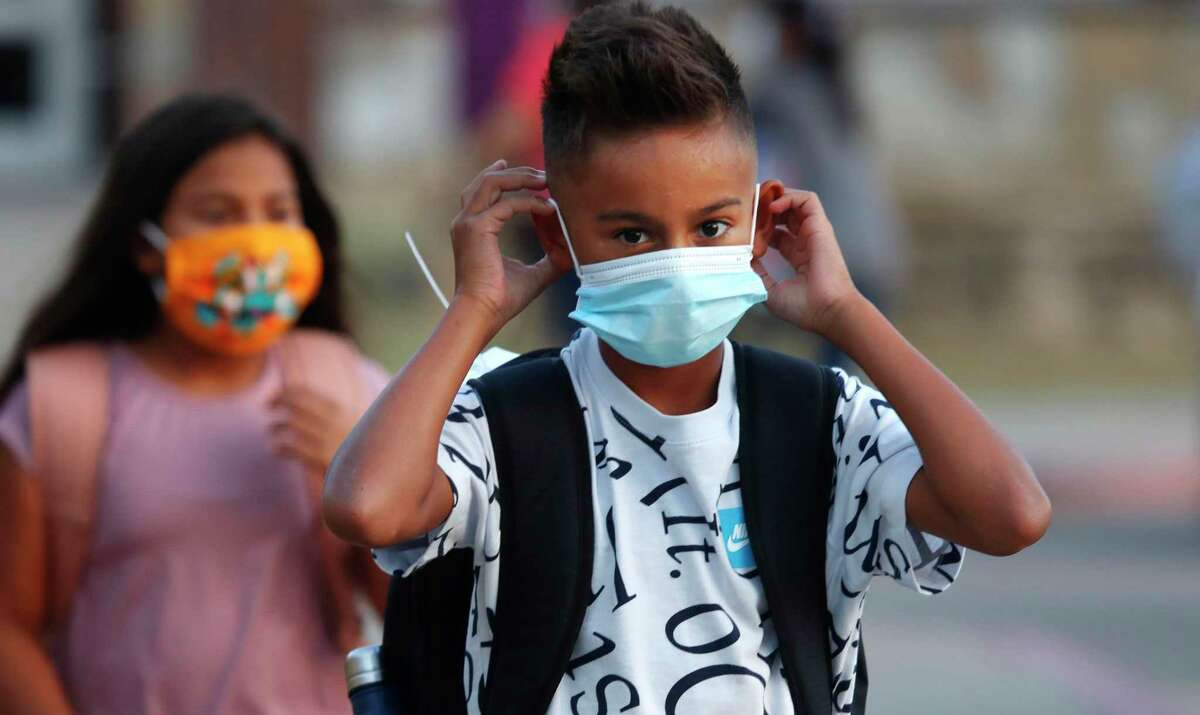 An elementary school student adjusts his mask as he arrives for classes in Godley in Johnson County; the rural district was among the first in Texas to head back to school for in-person classes.