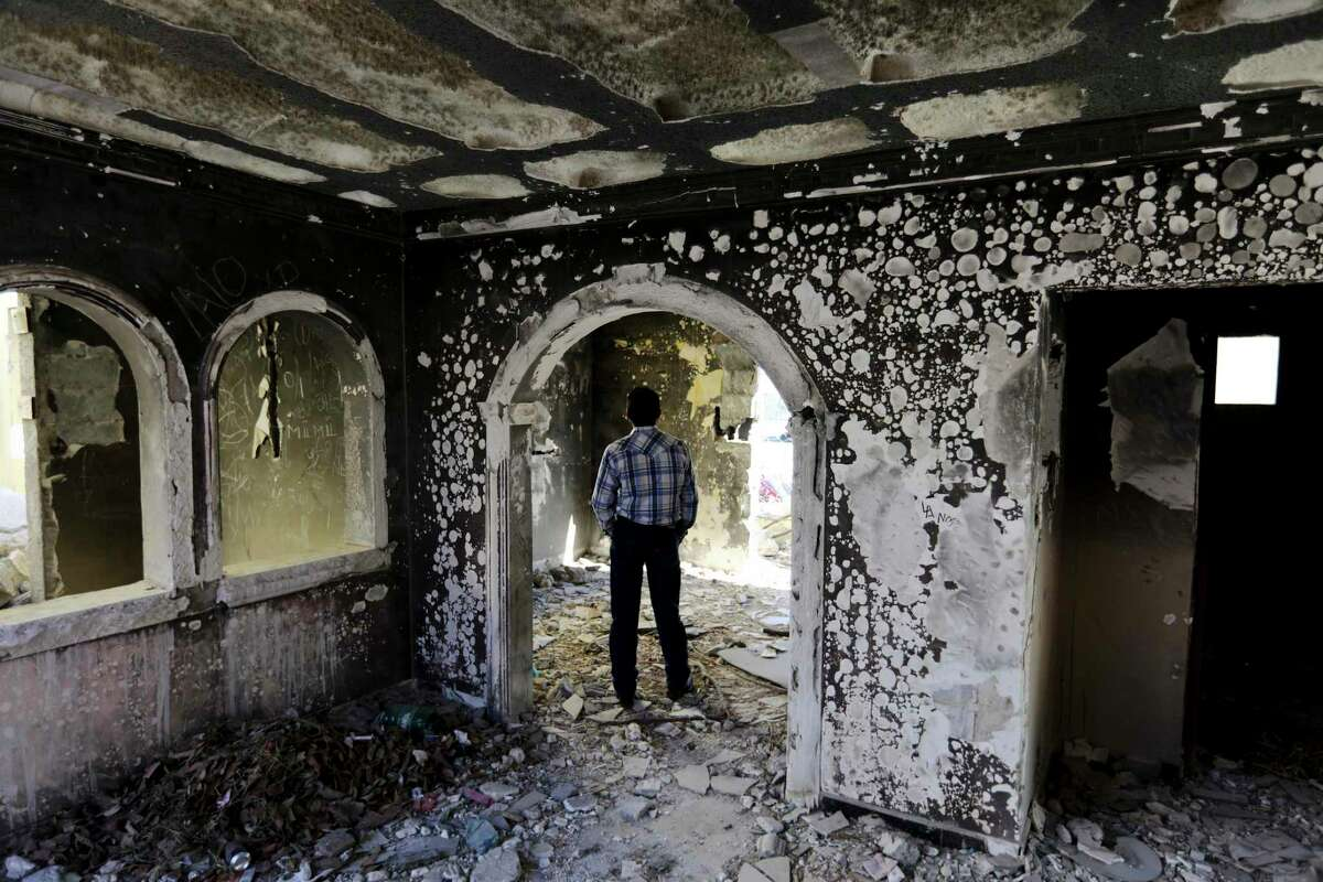 A former policeman walks through an abandoned home, torched by the Zetas cartel in 2011, in Allende, Coahuila state, Mexico, Tuesday, Dec. 3, 2019. Cartel members razed and burned houses and kidnapped people. Residents of Villa Union, 12 miles from Allende, said that they fear a return to the days of 2010-2013, when the old Zetas cartel killed, burned and abducted Coahuila citizens.