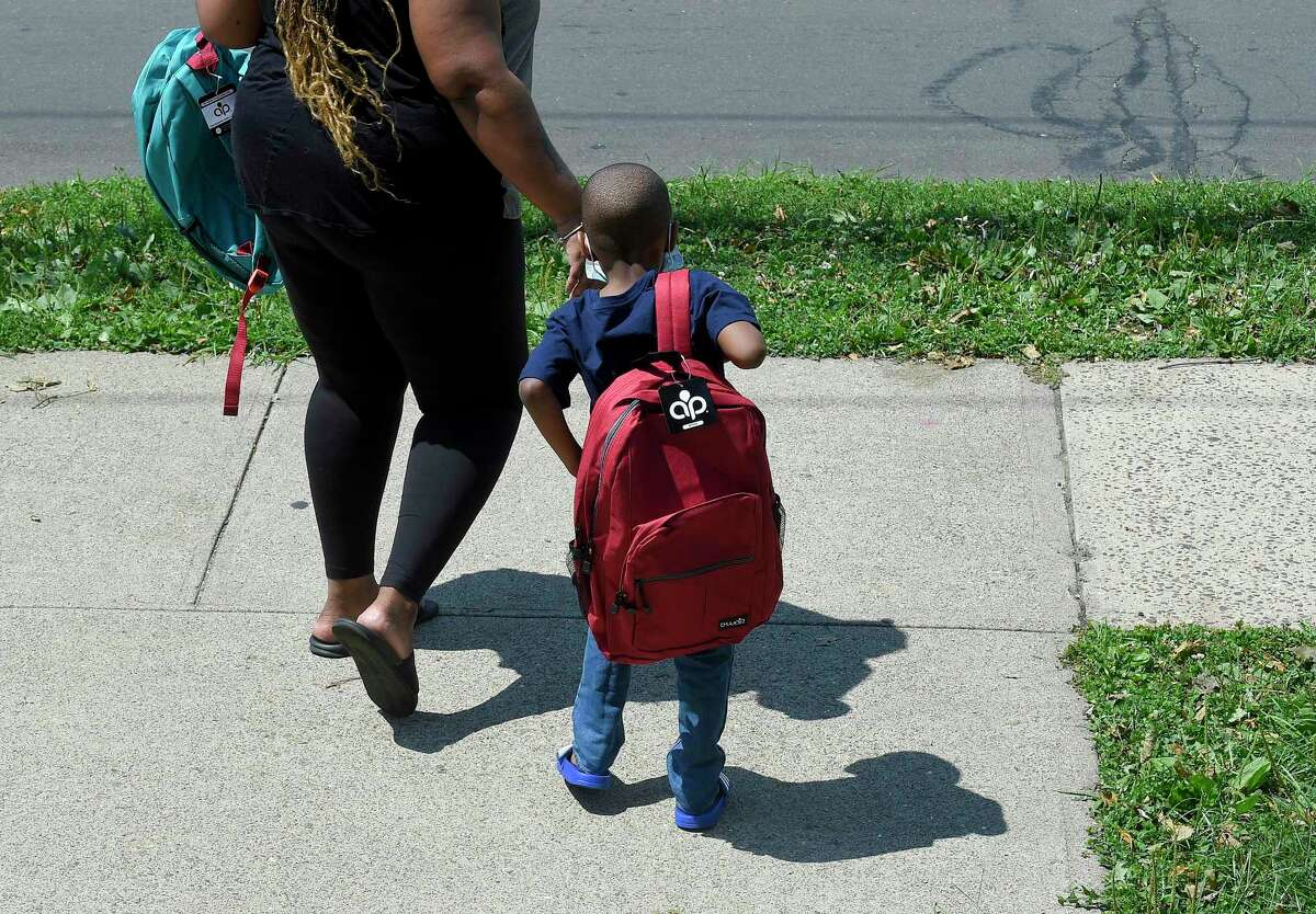 A young boy walks away with a new backpack that he received during a Back-to-School event hosted at the Bethel AME Church on Saturday in Stamford.