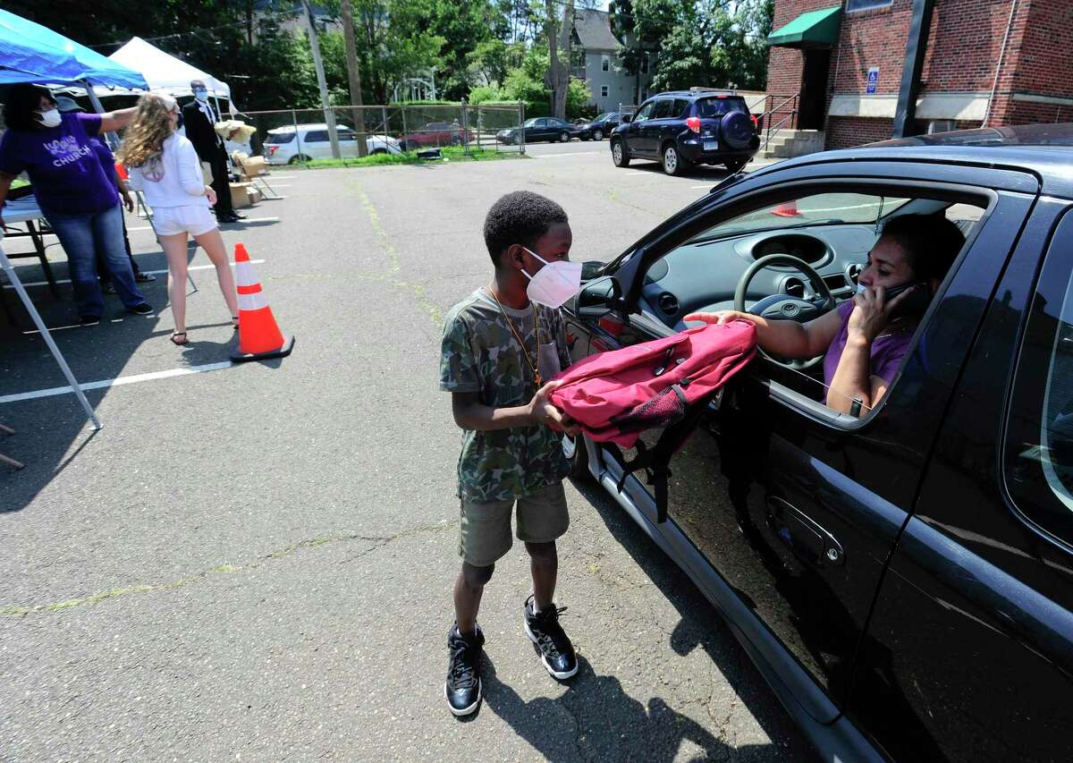 Robert Jackson Jr., 8, of Bridgeport helps distribute new backpacks to families during a Back-to-School event hosted at the Bethel AME Church on Saturday.