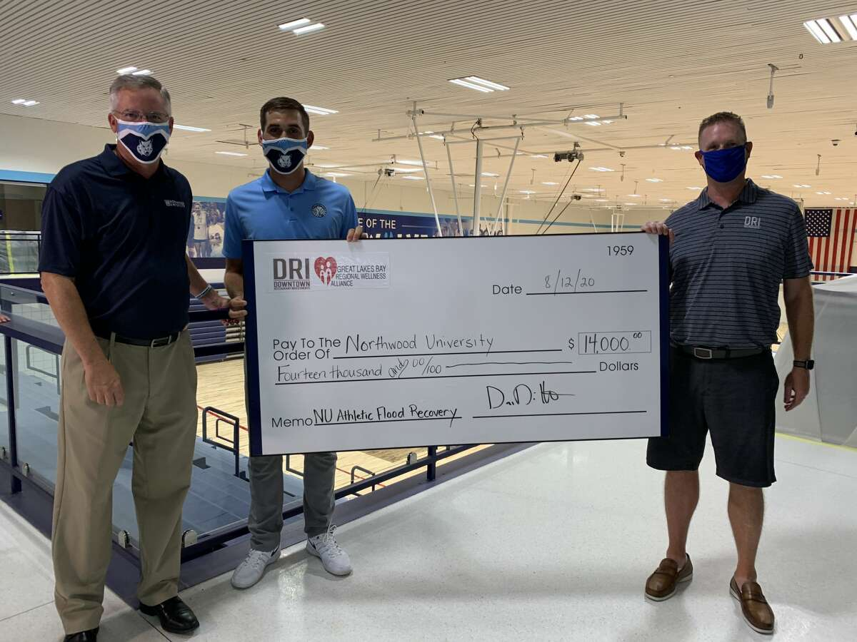 Northwood senior golfer Austin Deiters (center) and Dave Dittenber (right), proprietor of Downtown Restaurant Investments and chairperson of Great Lakes Bay Regional Wellness Alliance, present Northwood Athletics Director Dave Marsh with a check for $14,000 generated by two golf-related fundraisers for flood relief at NU's Riepma Arena on Aug. 12, 2020.
