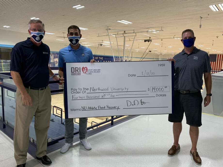 Northwood senior golfer Austin Deiters (center) and Dave Dittenber (right), proprietor of Downtown Restaurant Investments and chairperson of Great Lakes Bay Regional Wellness Alliance, present Northwood Athletics Director Dave Marsh with a check for $14,000 generated by two golf-related fundraisers for flood relief at NU's Riepma Arena on Aug. 12, 2020. Photo: Fred Kelly/fred.kelly@mdn.net