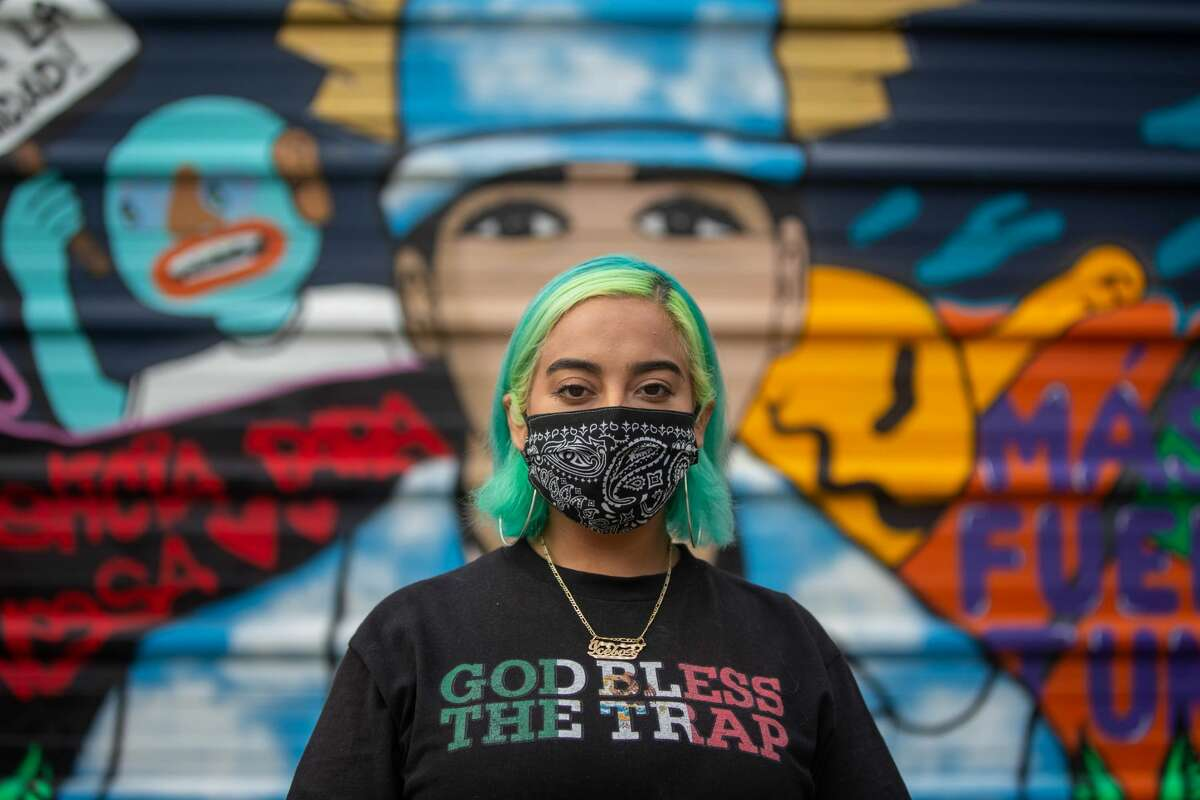 """Artist Amanda """"Ice Box"""" Quintanilla, 28, poses in front of her mural in memory of Vanessa Guillén on Canal Street, July 29. As a Chicana woman, Vanessa's death hit close to home. After hearing Mayra Guillén, Vanessa's sister, speak at a protest in Houston, Quintanilla immediately drove down to Latino's to paint the wall. """"You paint and get excited but when you take a step back it's a little heart breaking,"""" she said, """"For me, it's a form of protest and of mourning."""""""