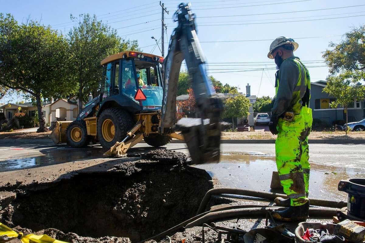 A team of six East Bay Mud employees help to brace one of a dozen main water line breaks in West Berkley on the morning of August 13, 2020.