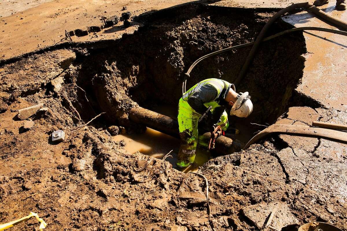 East Bay Mud employees work to stop a water line break in West Berkeley, CA on August 13, 2020.