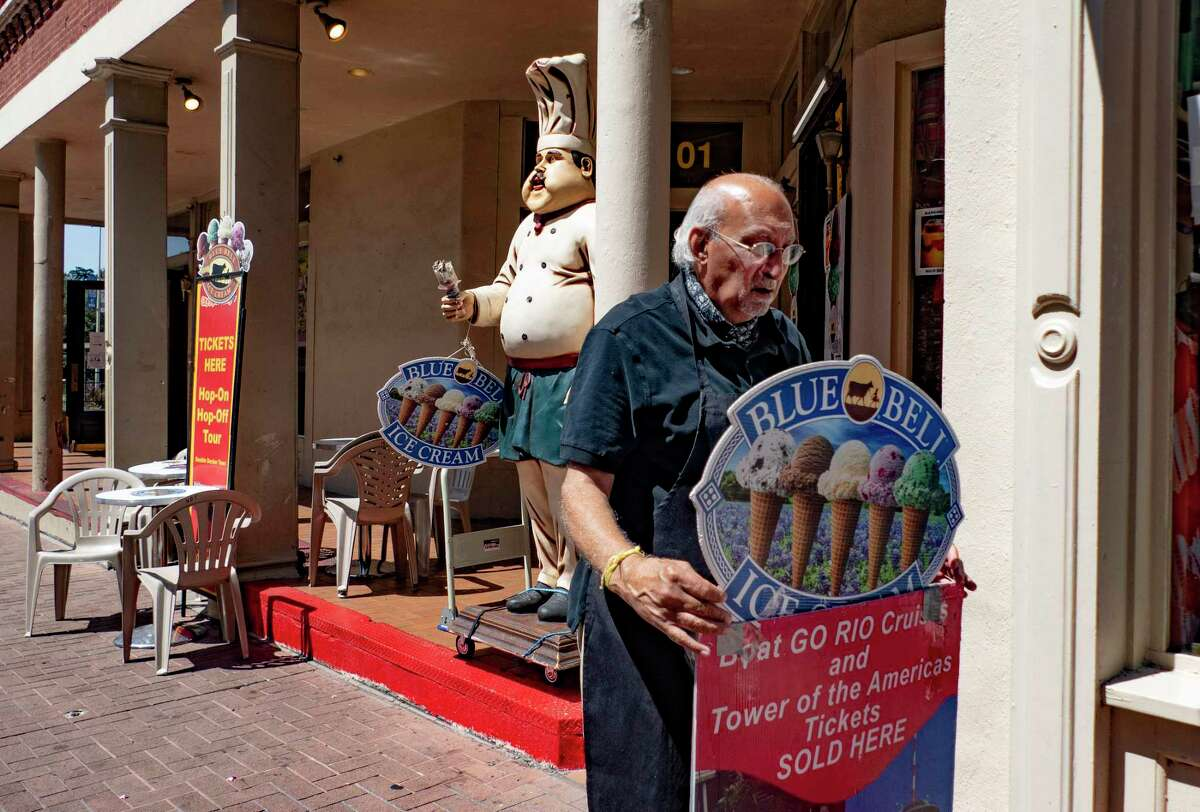 """Kiran Bhalla, owner of The Unofficial Best of Texas on Alamo Plaza, which sells ice cream, hats and other souvenirs, adjusts a sign in front of his store on Thursday, Aug. 13, 2020. Bhalla said that his business is down 70 percent because of the coronavirus pandemic. He has had to cut the hours of his employees. """"There is no hope on the horizon until the end of the year,"""" he said. """"Conventions and Air Force graduations have all been cancelled."""""""