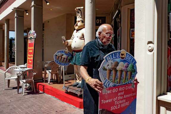 "Kiran Bhalla, owner of The Unofficial Best of Texas on Alamo Plaza, which sells ice cream, hats and other souvenirs, adjusts a sign in front of his store on Thursday, Aug. 13, 2020. Bhalla said that his business is down 70 percent because of the coronavirus pandemic. He has had to cut the hours of his employees. ""There is no hope on the horizon until the end of the year,"" he said. ""Conventions and Air Force graduations have all been cancelled."""