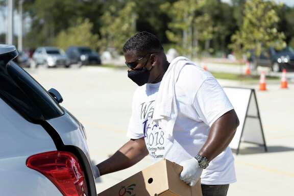 Charles Hayes loads a box of food into the back of a SUV during a food distribution event at Planet Ford Stadium in Spring, Tuesday, August 11, 2020. There will be two other Neighborhood Super Site Food Giveaway events held at Planet Ford Stadium on August 25 and September 8.